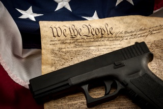 "The second amendment and gun control in america concept with a handgun and the american constitution on the USA flag with close up on the ""we the people"" part of the united states constitution"